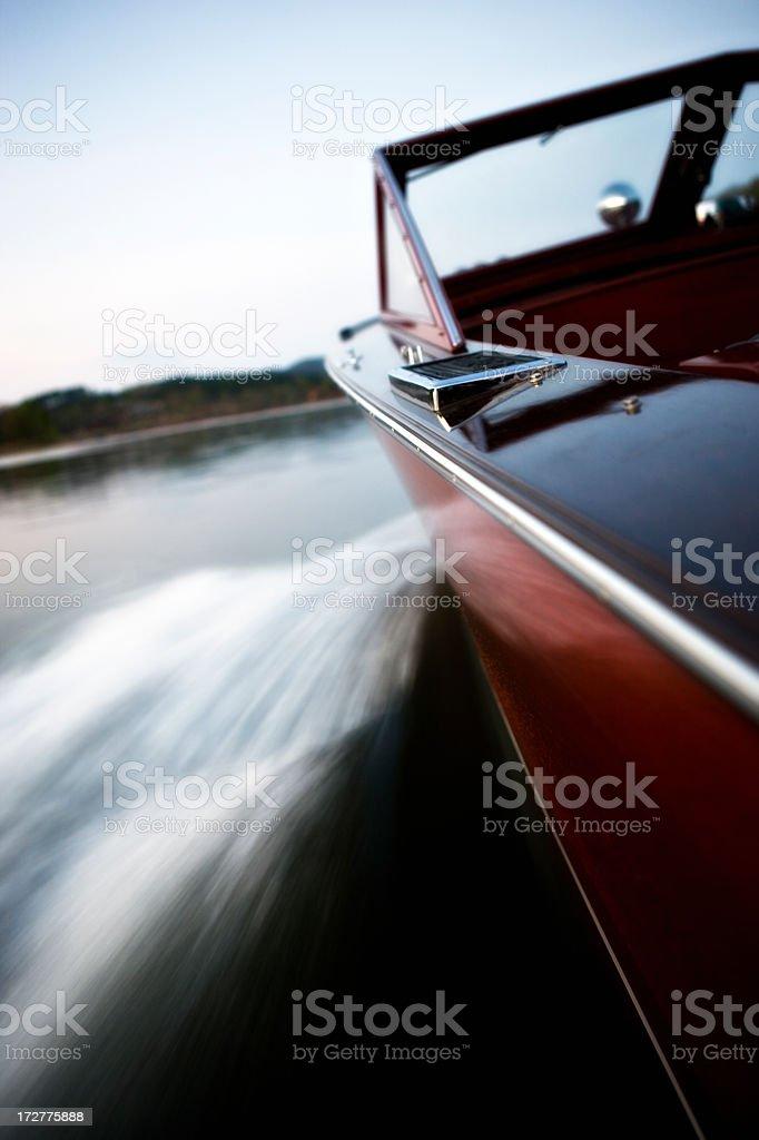 Long exposure of classics wooden boat cruising the lake royalty-free stock photo