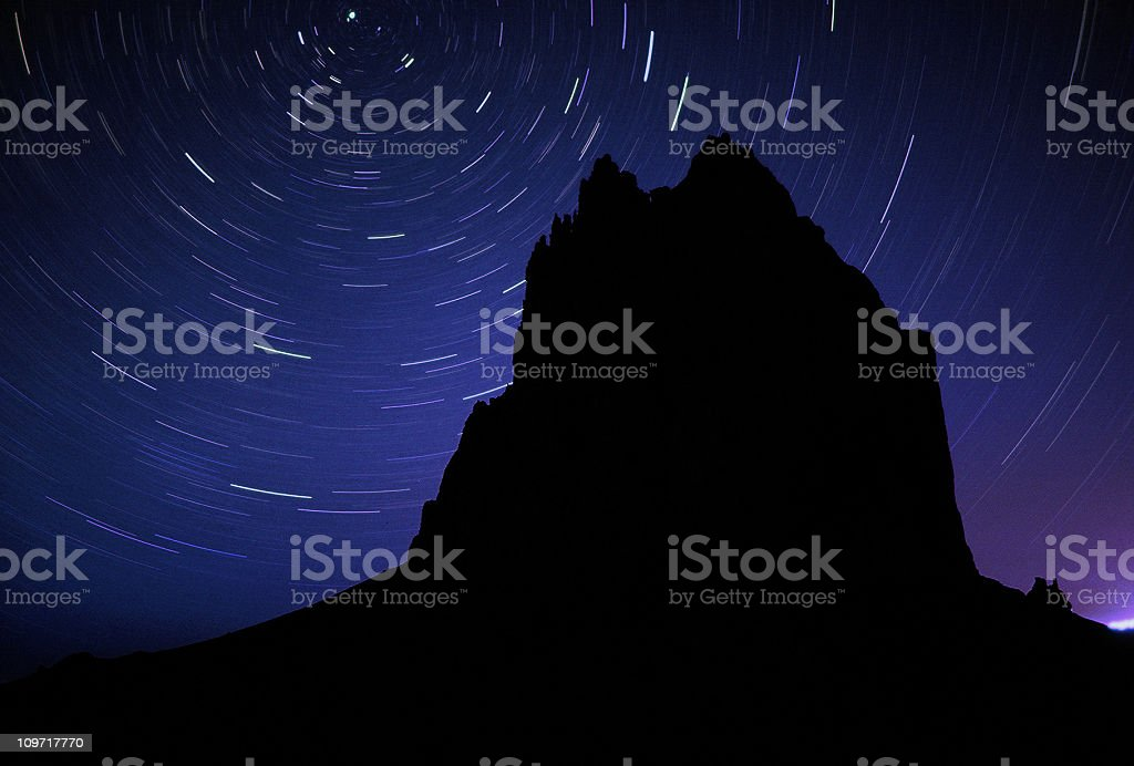 Long Exposure of Stars and Rock Silhouette stock photo