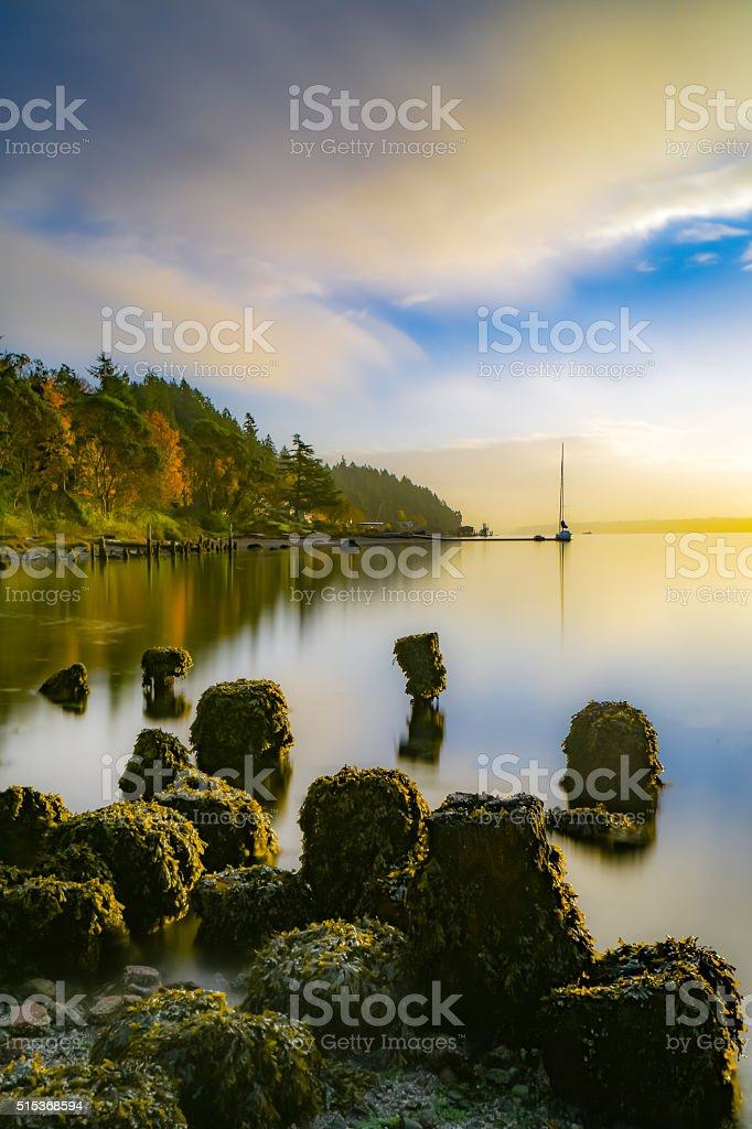 Long exposure sunrise, sailboat, old pilings, fall color stock photo