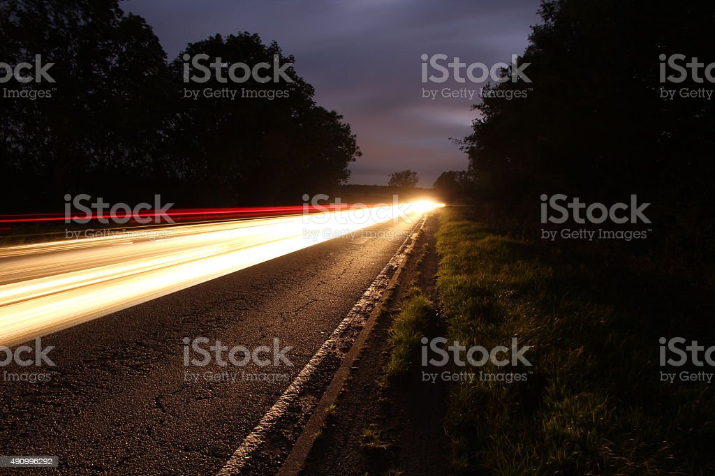 Long exposure vehicle lights country road stock photo