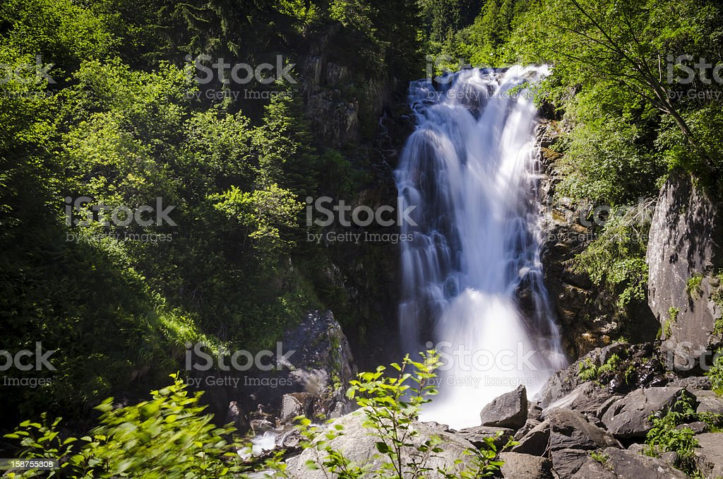 long exposure watefall sorrounded by rocks and trees royalty-free stock photo