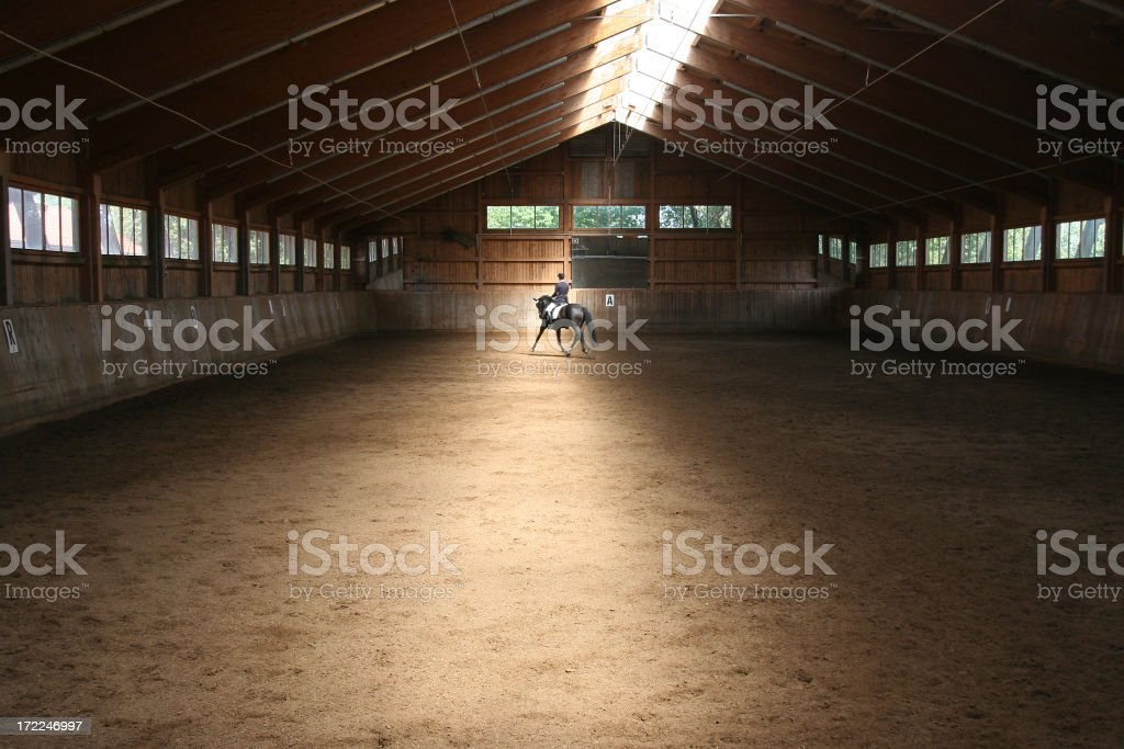 Long farm cabin with a man riding a horse stock photo