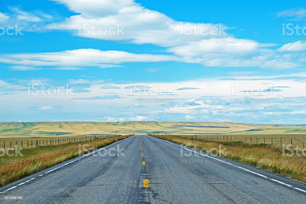 Long flat road under a blue sky. stock photo