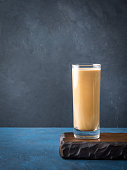 Long glass with coffee and cream on dark background