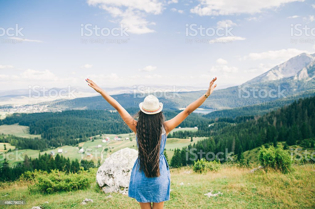 long hair woman travel in mountains landscape back view stock photo