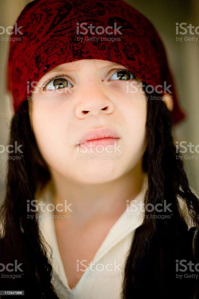 Long- haired child with red cap looking up. royalty-free stock photo