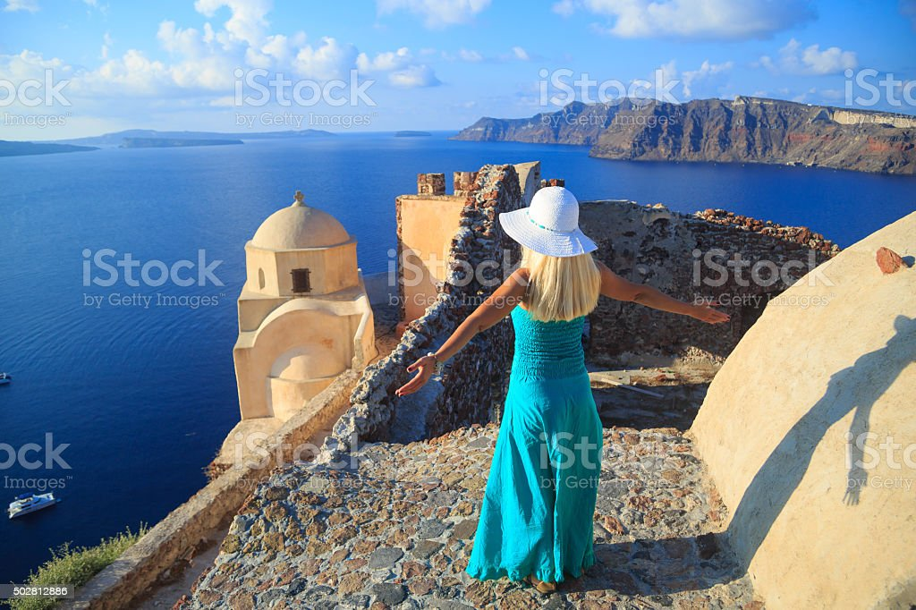 Long haired woman with beach hat in Oia, Santorini stock photo