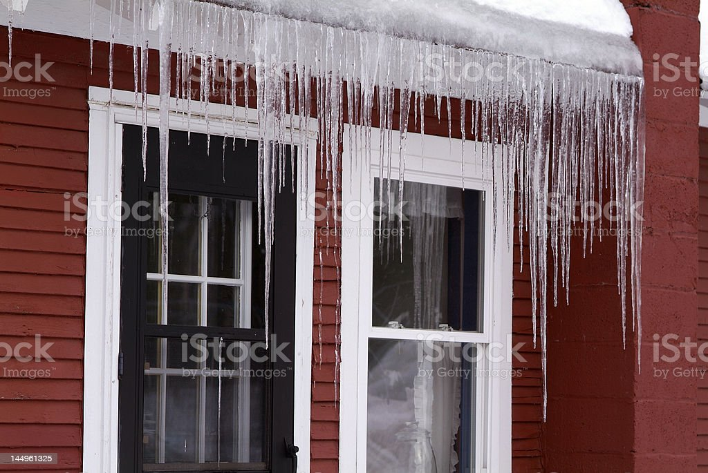 Long icicles dangling from a red house in winter royalty-free stock photo