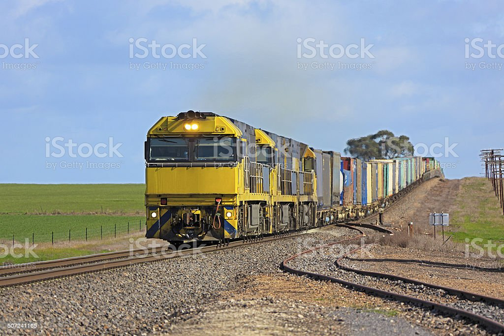 Long intermodal freight train in green countryside stock photo