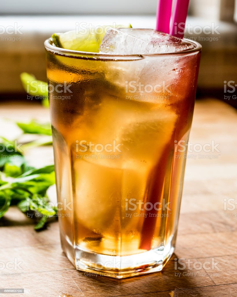 Long island iced tea cocktail with lime, ice and served with pink straw. stock photo
