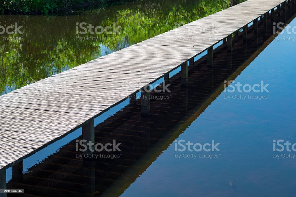 Long jetty across a large pond sideview stock photo