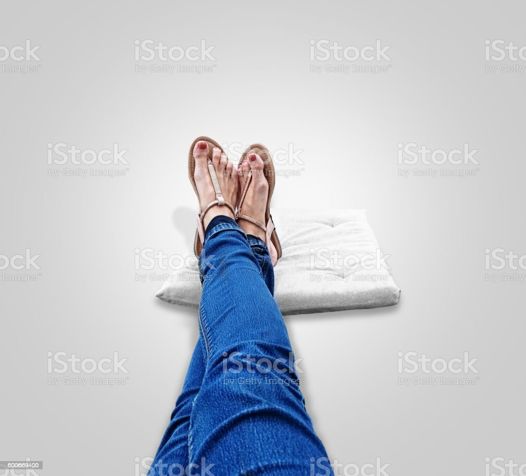 long legs with sandals on her feet on a cushion stock photo