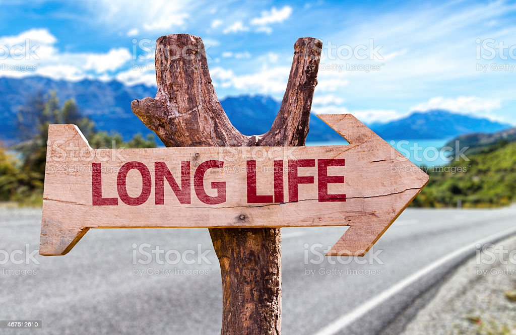 Long Life wooden sign with a street background stock photo