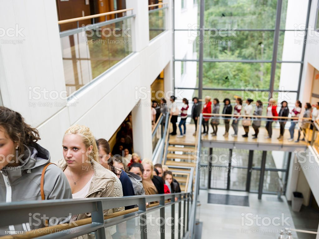 A long line of people up a large stairwell stock photo