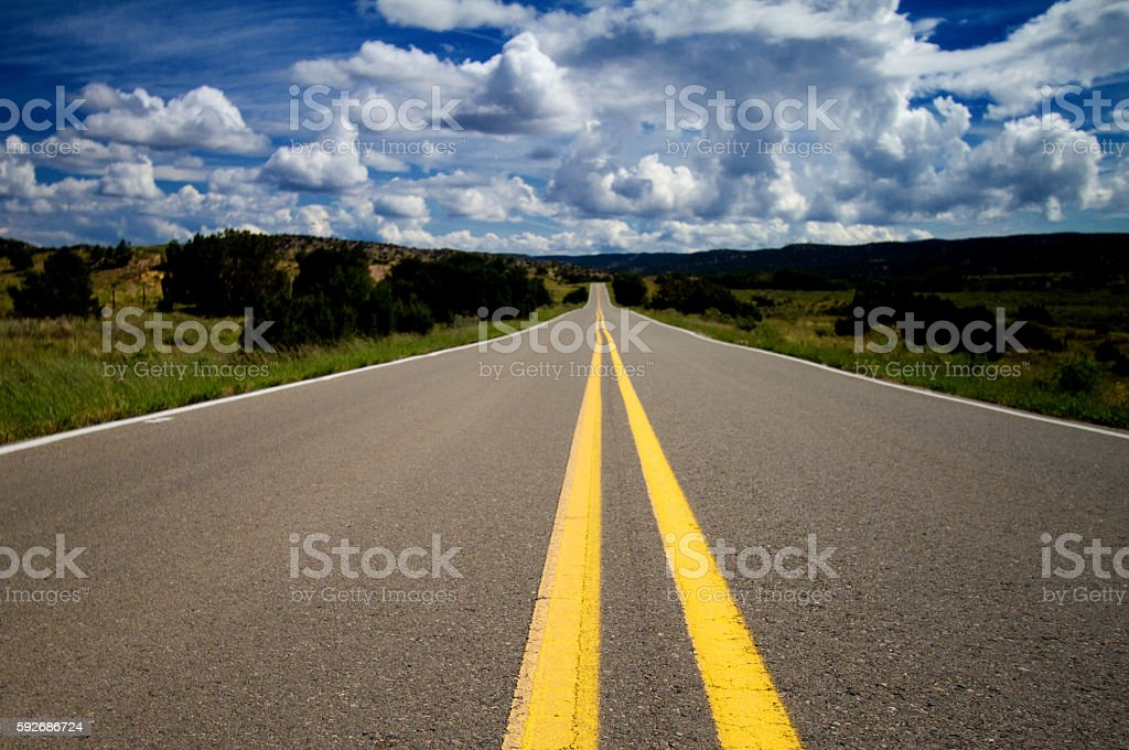 Long Lonely Highway: Double Yellow Line Heading toward Thunder Cloud stock photo