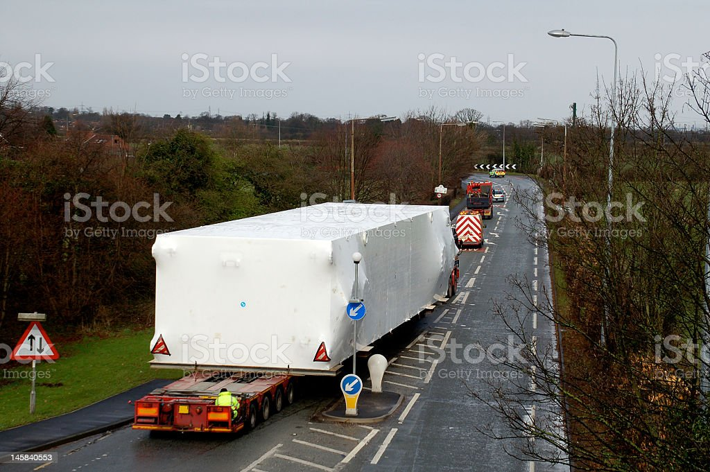 Long lorry carrying a wide load down a road stock photo