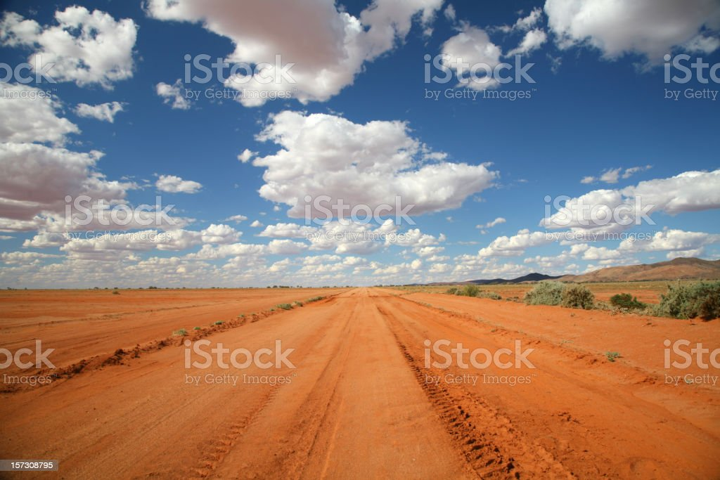 Long orange outback road under a blue sky stock photo