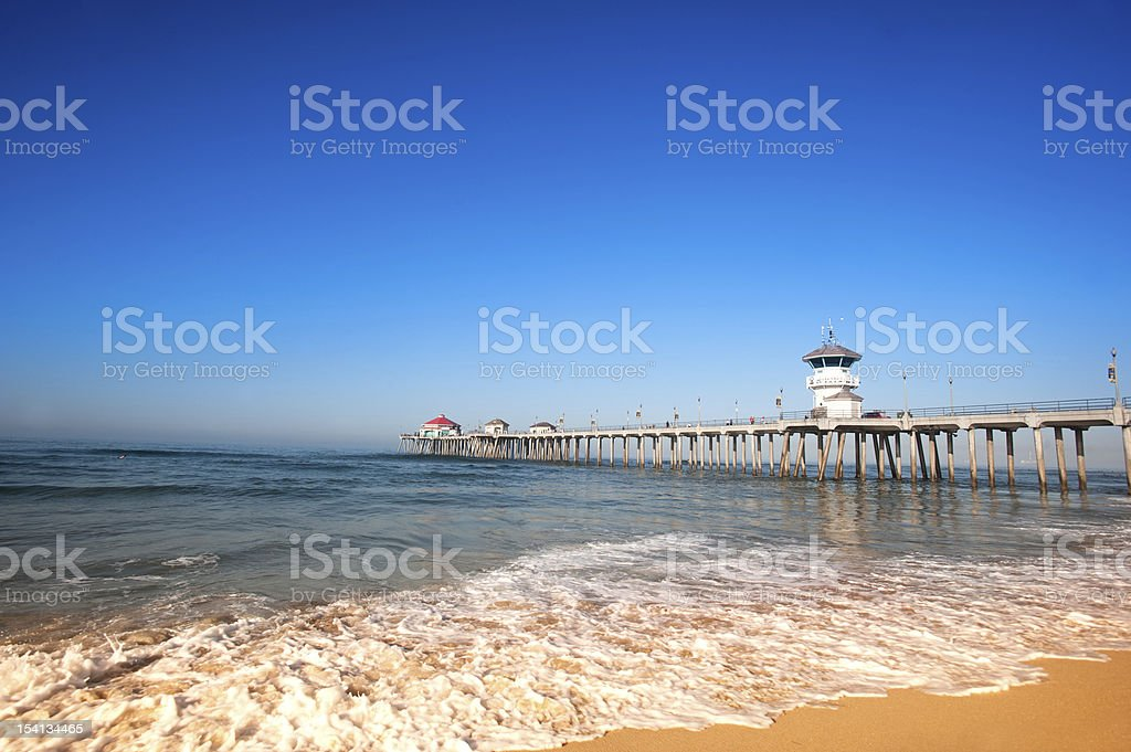 Long pier at a beach on a clear sunny day stock photo