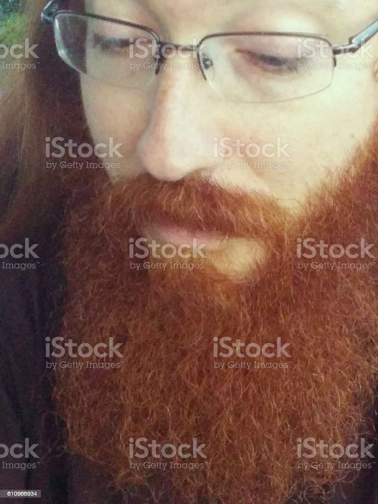 Long Red Hair Bearded Hippie Artist Man, Glasses, Looking Down stock photo