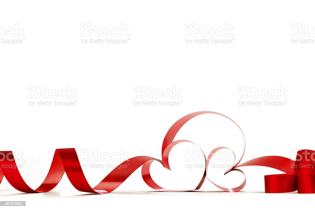 Long red ribbon forming heart shapes in a white background stock photo