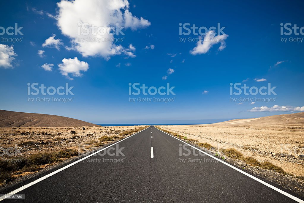 Long road in the desert heading into a blue sky stock photo