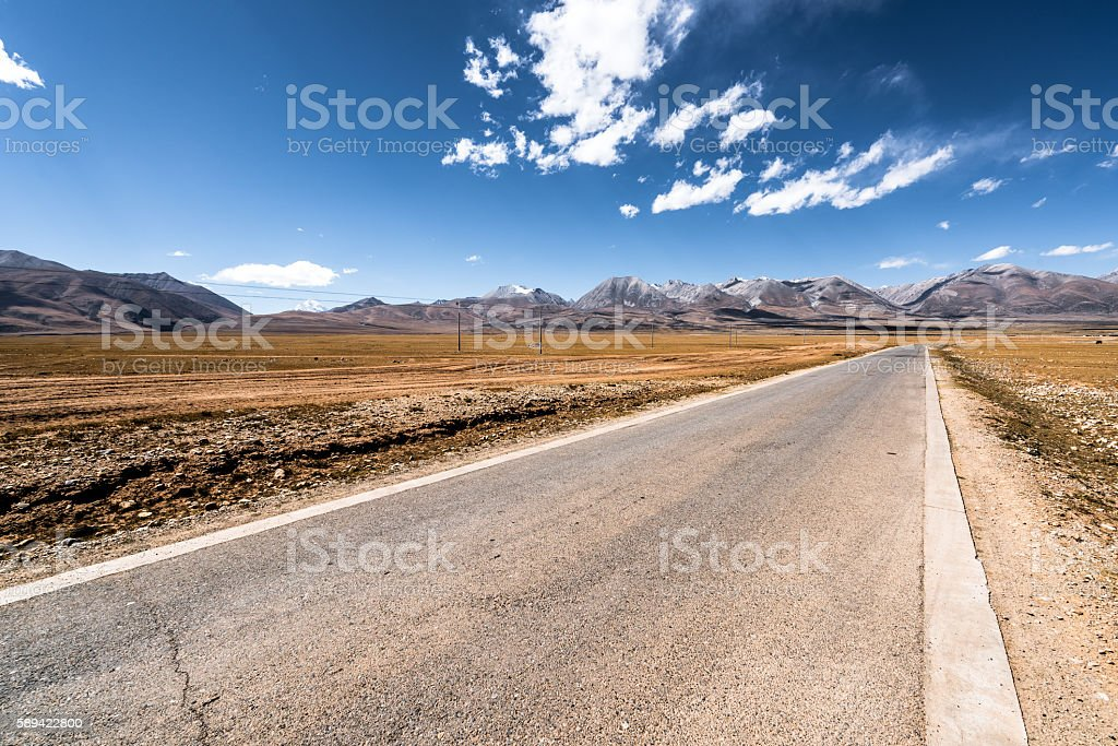 Long road leading towards mountains stock photo