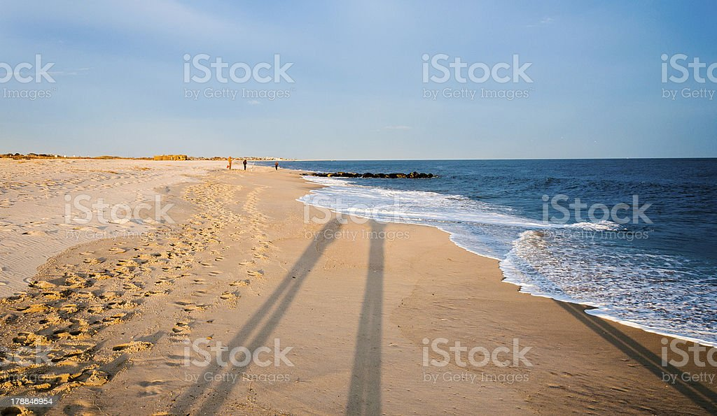 Long shadows on the beach at Cape May, New Jersey. stock photo