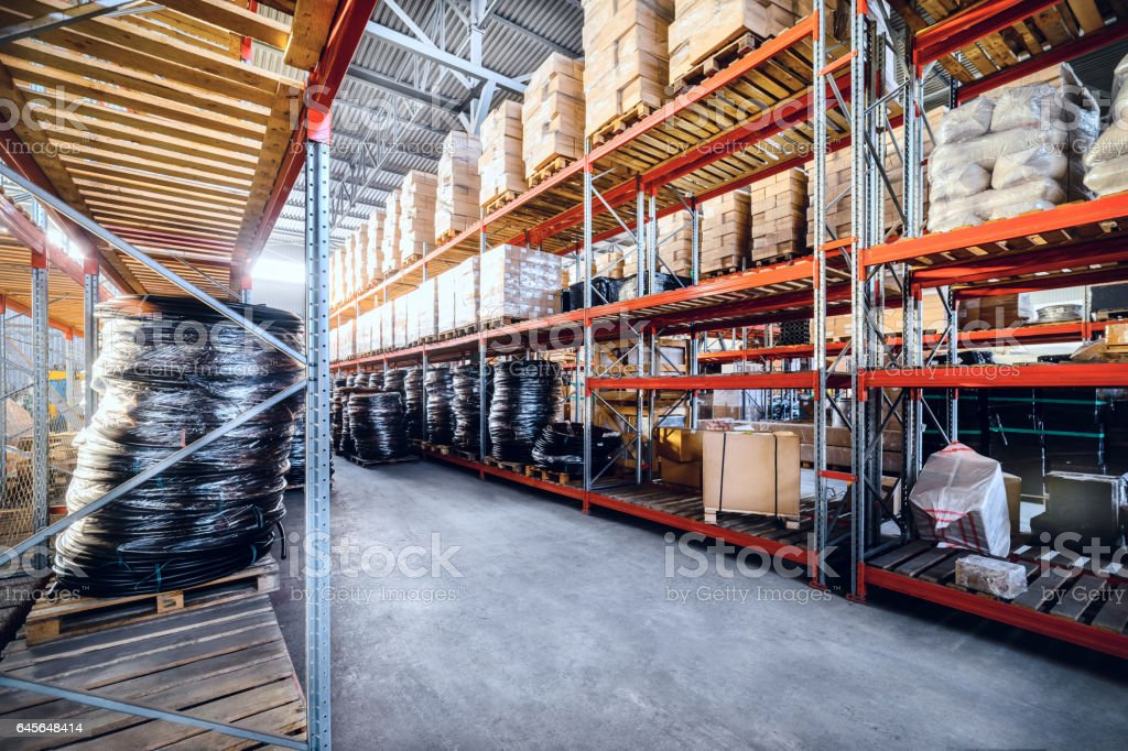 Large industrial warehouse. Long shelves with a variety of boxes and...