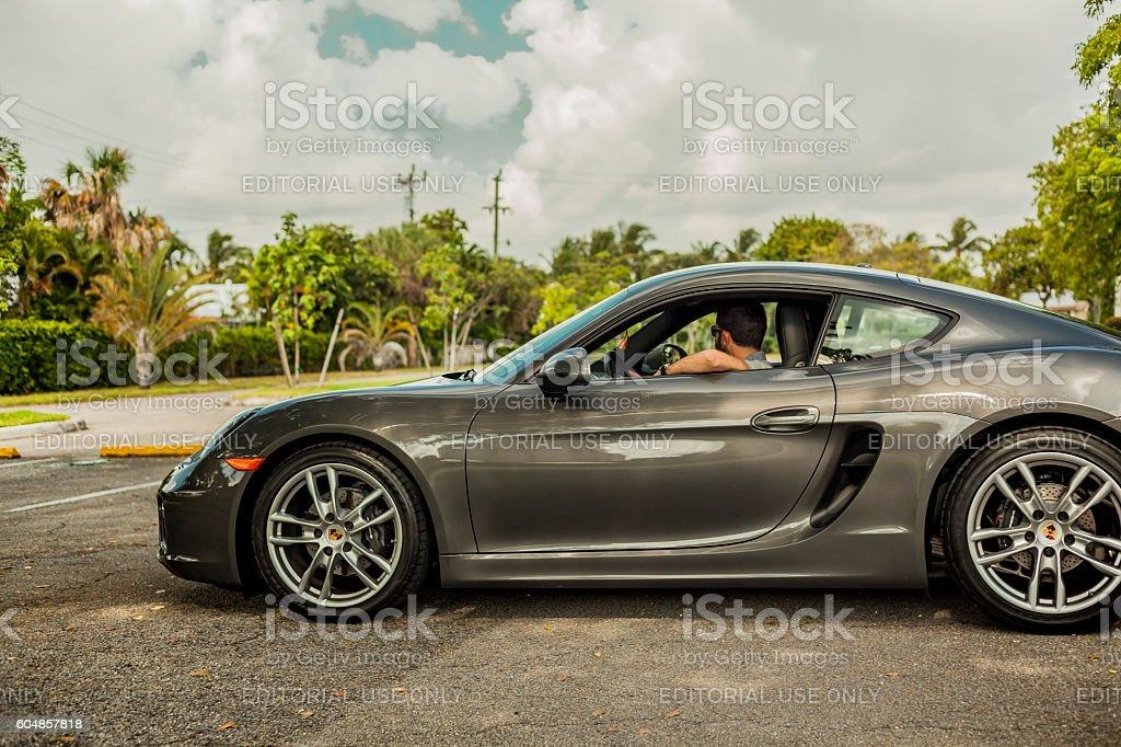 Long shot of a young man driving a Porsche Cayman stock photo