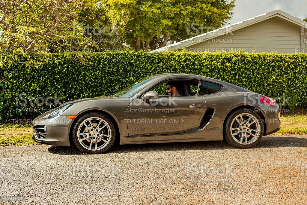 Long shot of a young man inside a Porsche Cayman stock photo