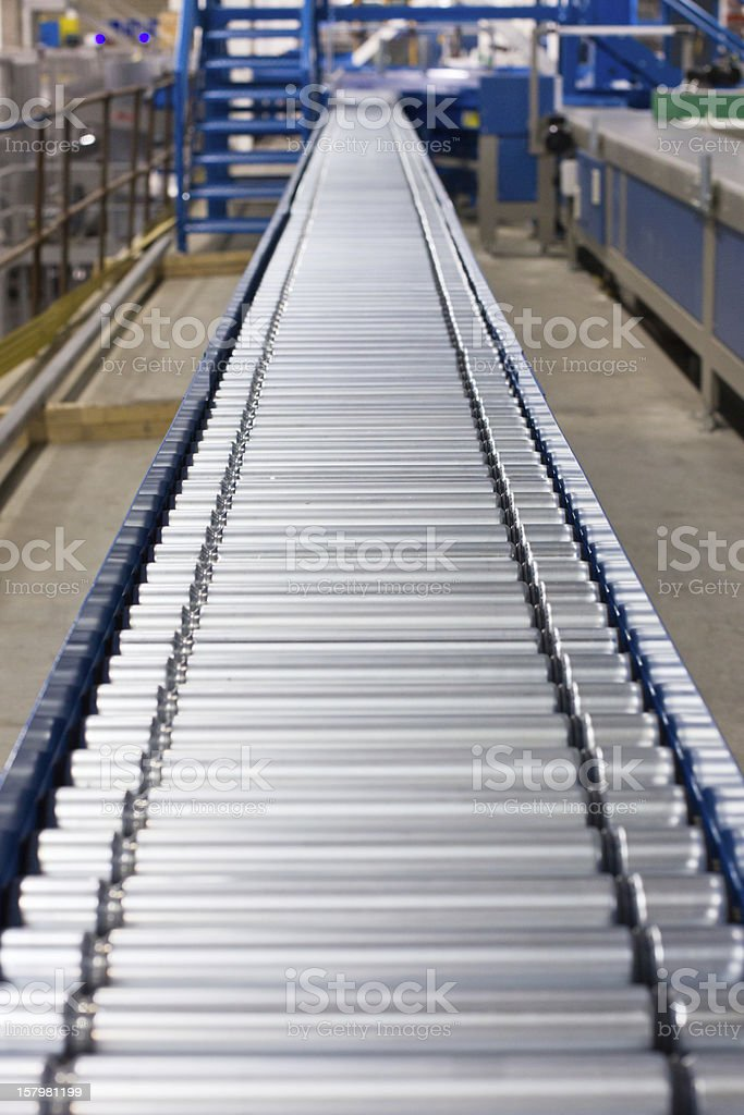 A long silver conveyor belt in a factory  stock photo