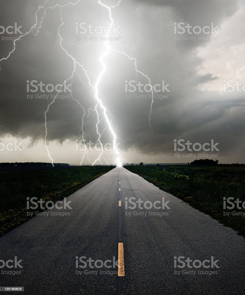 Long straight road meeting a lightning bolt stock photo