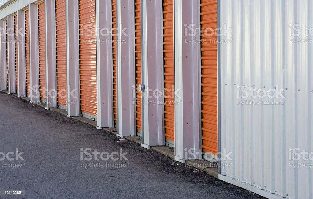 A long stretch of orange shutter doors all drawn down royalty-free stock photo