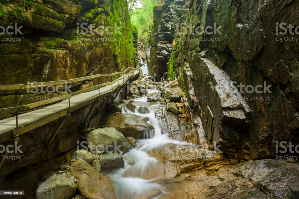 long suspended bridge surrounded by rocks in new hampshire stock photo