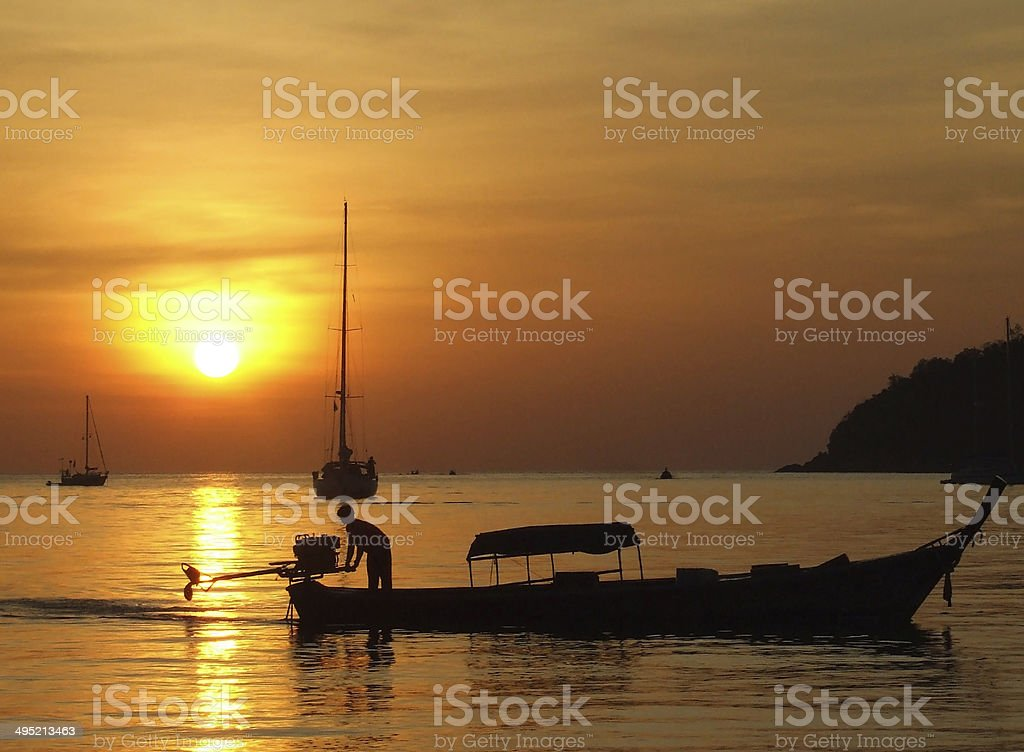 Long tail boat and sunset with a man royalty-free stock photo