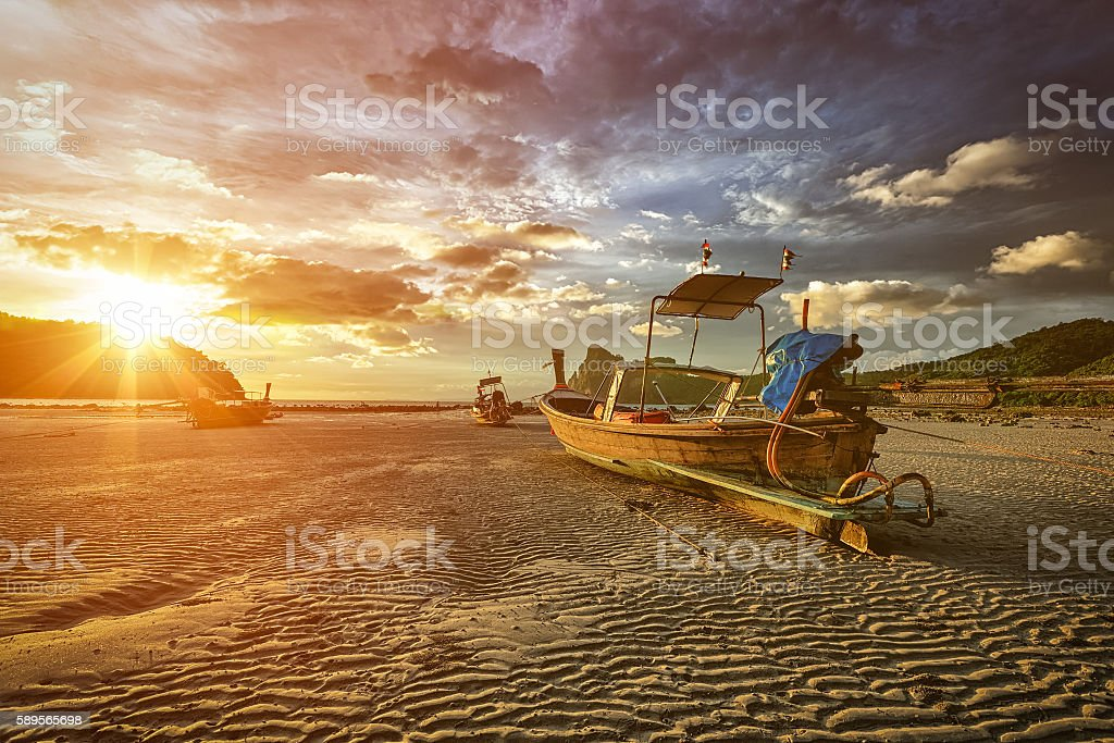 Long tail boat at beach on sunset stock photo