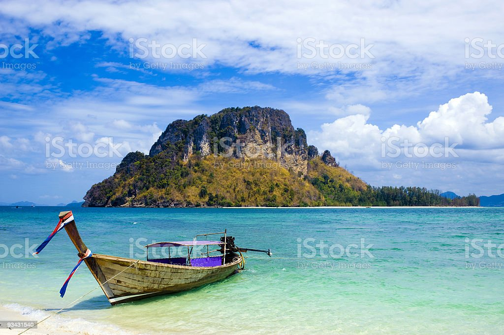 A long tail boat on shore in Thailand stock photo