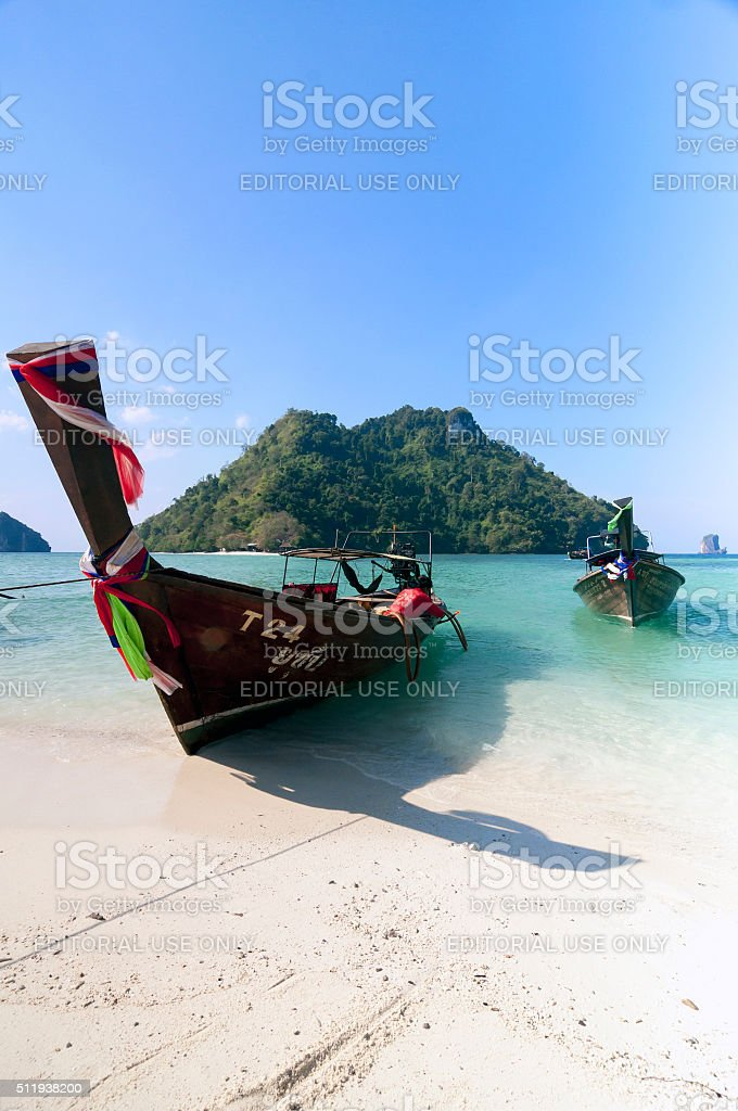 Long tail boat on tropical beach with limestone rock. stock photo