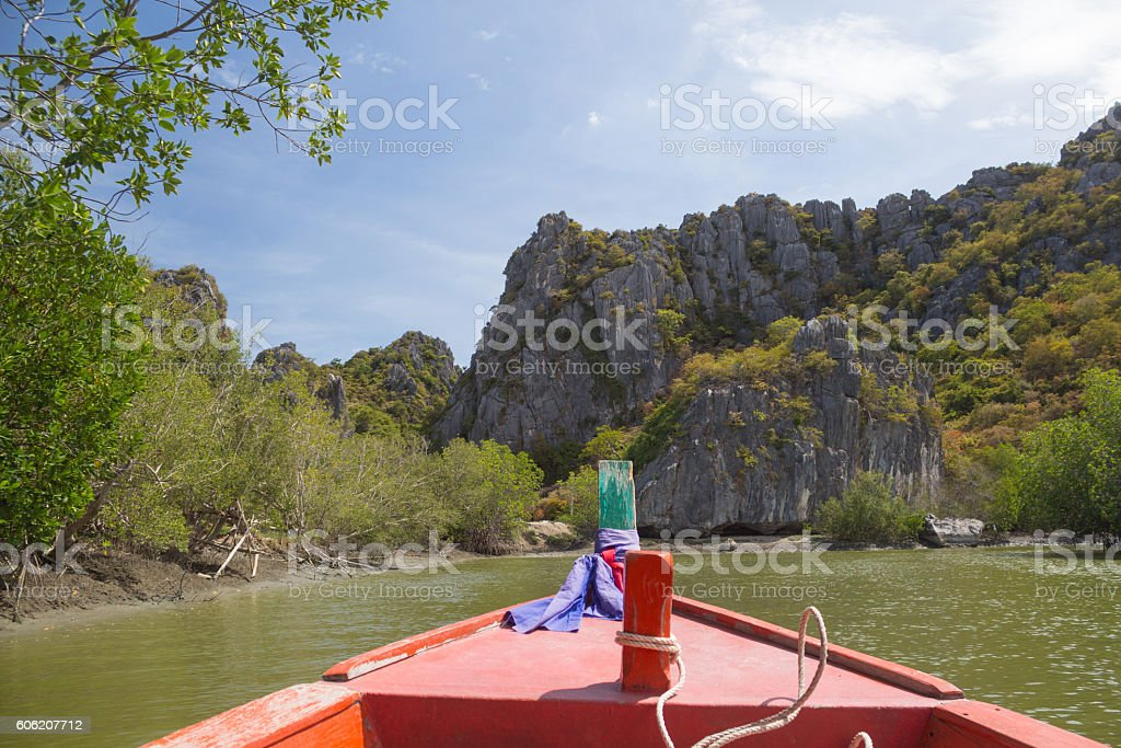 long tail fishing boat floating in sea with limestone mountains Стоковые фото Стоковая фотография