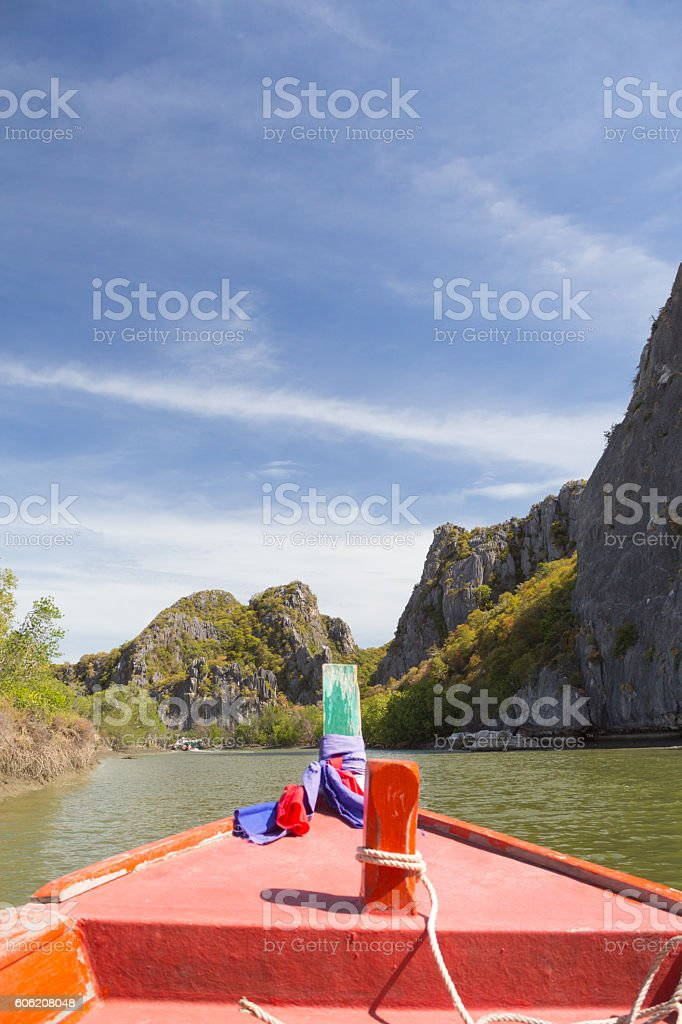 long tail fishing boat floating in sea with limestone mountains Стоковые фото Стоковая фотография
