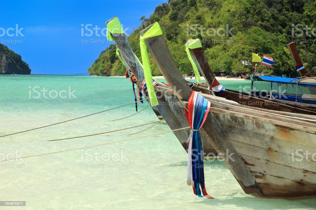 Long tail wooden boats moored on the beach stock photo