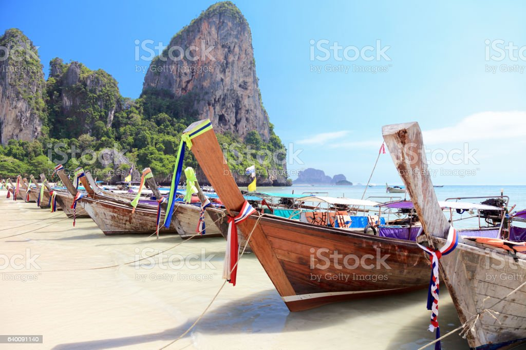 Long tail wooden boats stranded at the beach stock photo