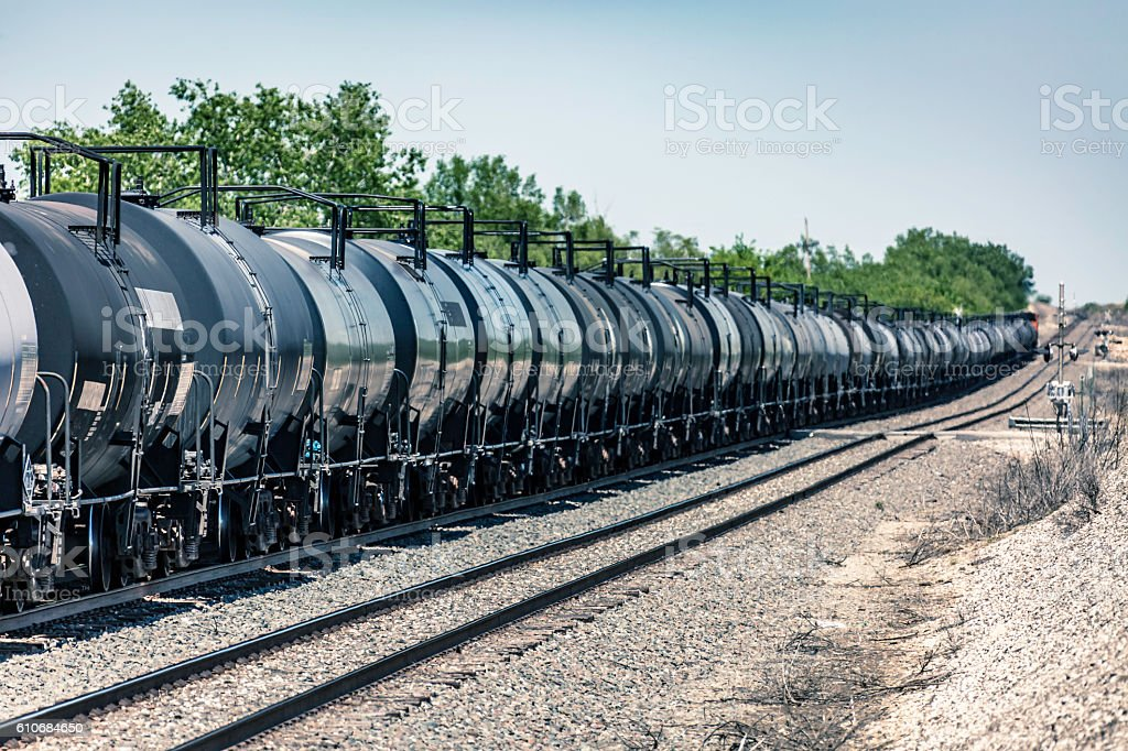 Long train of oil tank cars passing road crossing stock photo