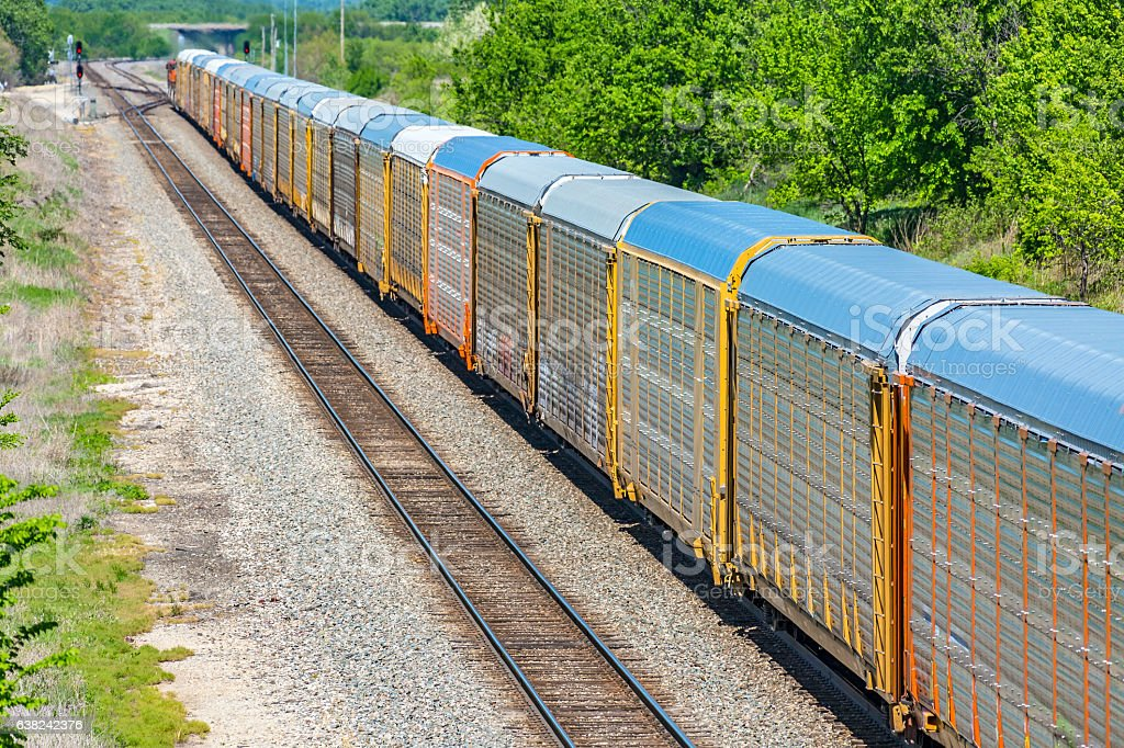 Long train transporting new motor vehicles in covered autoracks stock photo