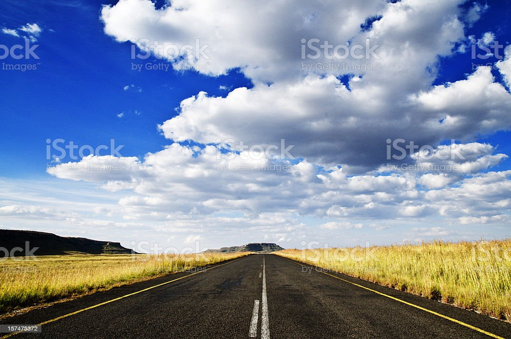 Long view of an empty road near a field on a sunny day royalty-free stock photo