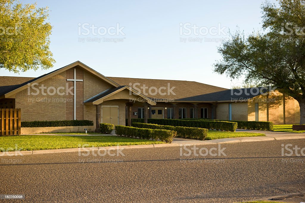 Long view of the front of a brown brick church with a cross stock photo