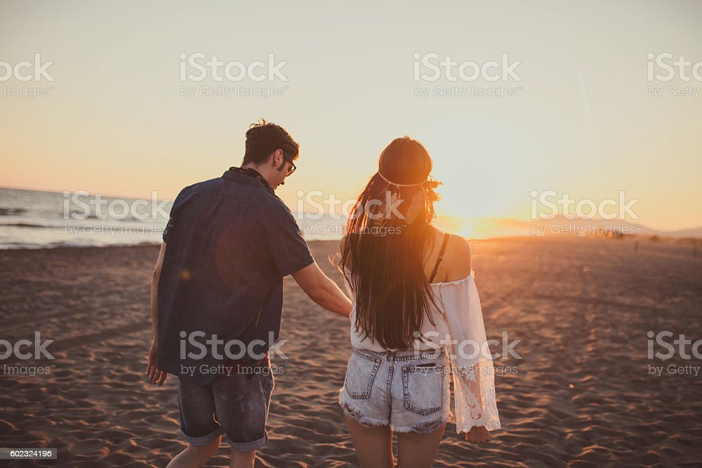 Long walks on the beach, sunset, young couple stock photo
