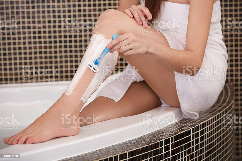 Long Woman Legs . Woman Shaving Legs in Bathroom stock photo