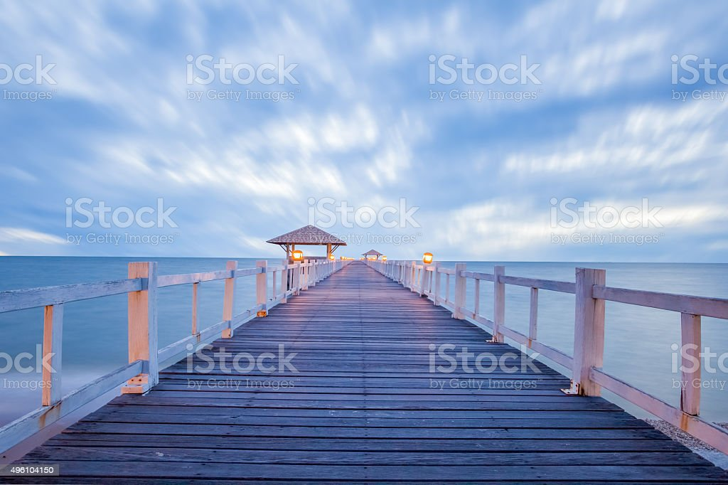 Long wood bridge at sea in sunset time stock photo