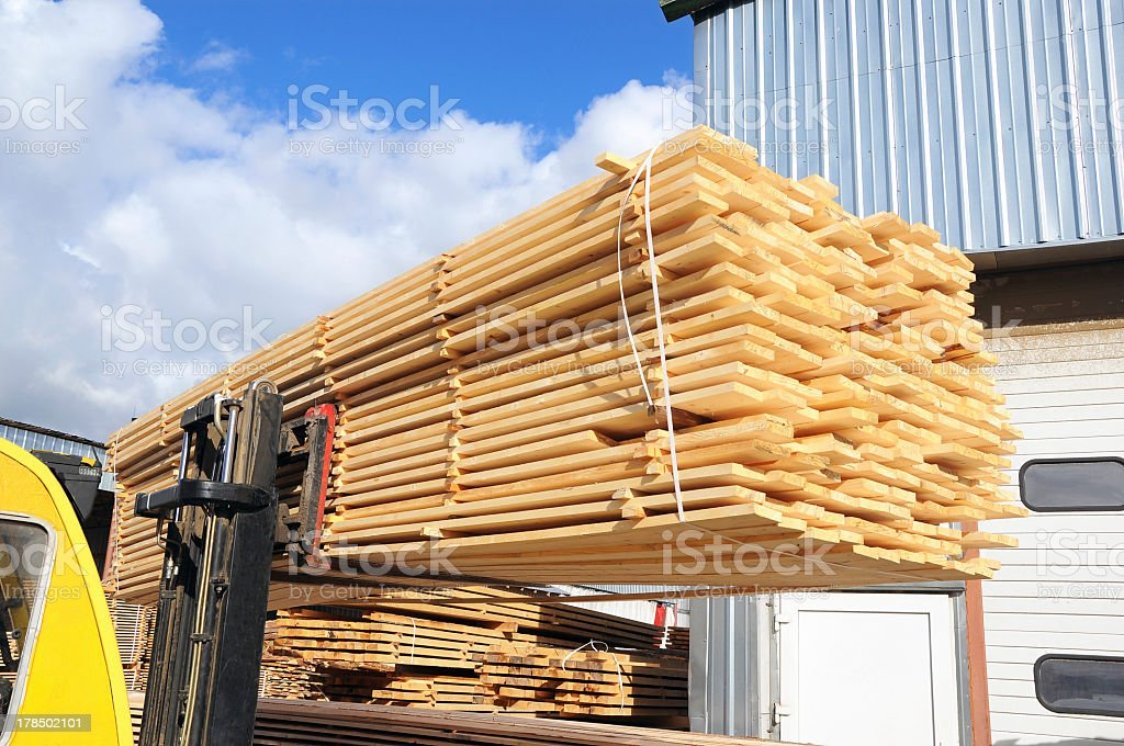 Long wooden planks stack and bundled in the timber yard stock photo